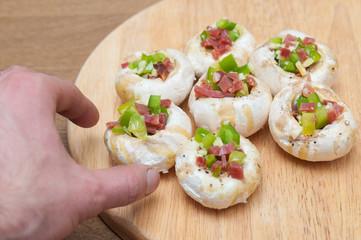 Preparing mushrooms stuffed with ham and pepper