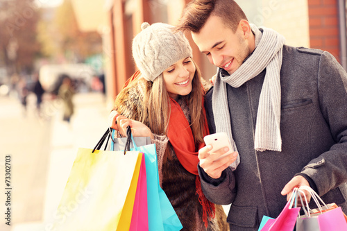 Happy couple shopping in the city with smartphone - 73302703