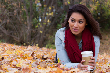 Woman lying on autumn leaves with coffee looking away