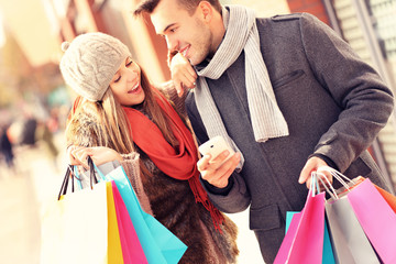 Joyful couple shopping in the city with smartphone
