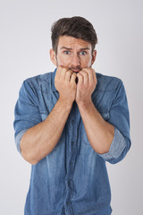 Man biting nails in fear