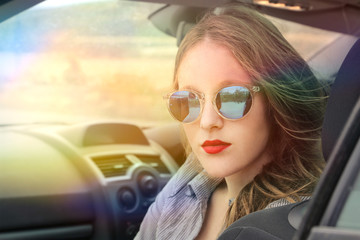 Fashionable girl sitting in a car