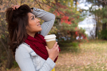 Stylish young woman with coffee outdoors during autumn