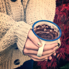 Close-up on girl hands with sweater holding a hot chocolate