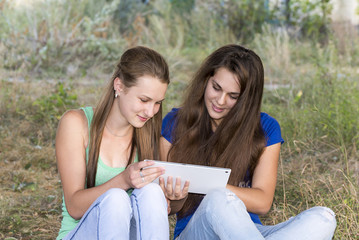 Two teen girls with your Tablet-PC in nature