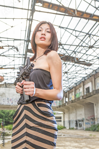 canvas print picture Asian woman with a gun in ruins