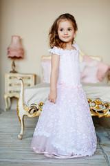 Красивая девочка в пышном платье в детской комнате