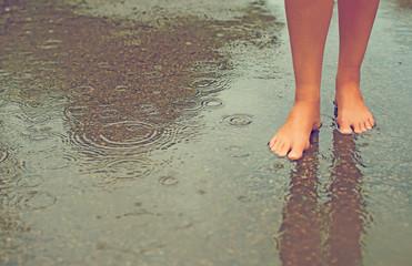 Woman enjoying tropical rain. Legs.