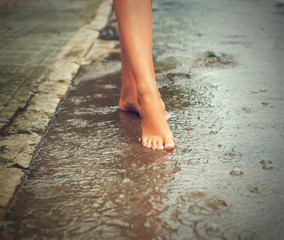 Woman enjoying tropical rain. Legs.