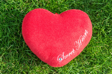 red fabric heart love on green grass