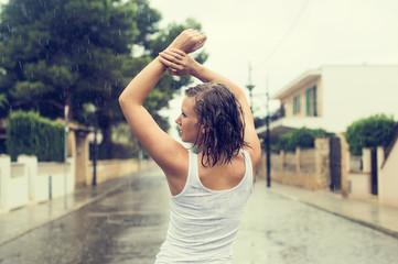 Happy blonde woman enjoying tropical rain. Vintage effect photo.