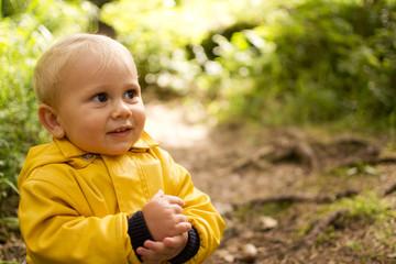 Bambino biondo felice nel bosco