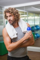Handsome man holding water bottle at gym