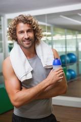 Smiling handsome man holding water bottle at gym