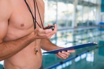 Mid section of shirtless coach with stopwatch by pool