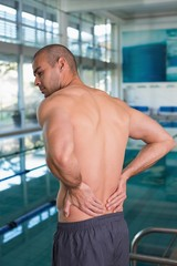 Rear view of shirtless swimmer with back ache by pool