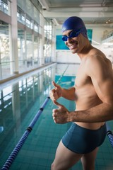Swimmer gesturing thumbs up by pool at leisure center