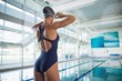 Rear view of a fit swimmer by pool at leisure center - 73307578