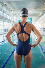 Rear view of fit swimmer by pool at leisure center
