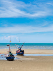 Old fishing boat stranded on a beach in sunny day, Thailand