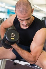 Young man exercising with dumbbell in gym