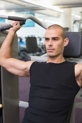 Serious young man working on fitness machine at gym