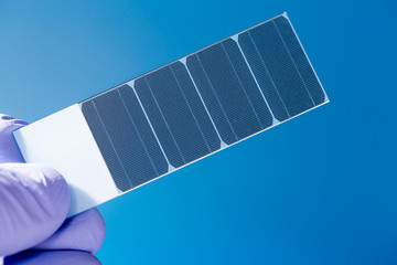 silicon crystal with photovoltaic cells in the hand of the scien
