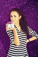 A shot of attractive young woman with a gift box in her hand