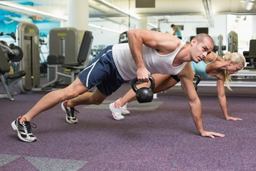 Fit couple doing push ups with kettle bells in gym