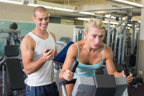 canvas print picture Trainer timing his client on exercise bike at gym