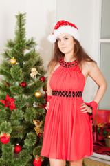 lass wearing red dress and xmas hat stands near New-Year's tree