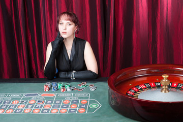 sexy girl wearing black dress and gloves plays in casino