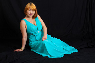 young blonde woman wearing a long blue dress sitting