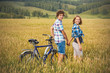 Teenage girl and boy on a bicycle in a summer field of rye