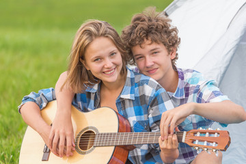 Teenage boy and girl near the tent playing a guitar outdoors