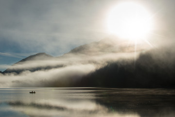 sunrise at autrian lake with fisher boat with dust
