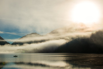 mystic dust over austrian alps lake with fisher boat and fog