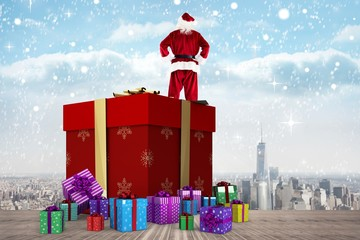 Composite image of santa standing on giant present