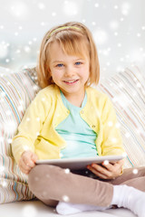 smiling girl with tablet pc computer at home