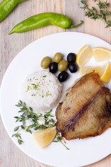 fried tilapia served with rice and herbs
