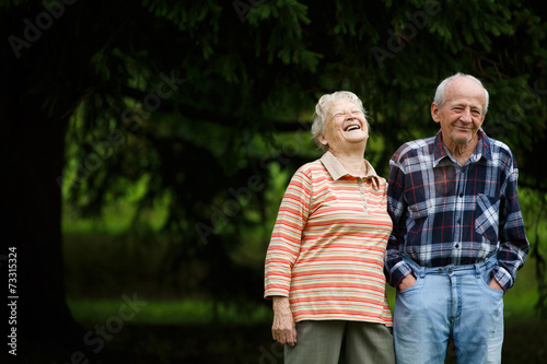 Happy senior couple looking at camera and laughing - 73315324