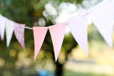 Fototapety Colorful bunting flags against green trees