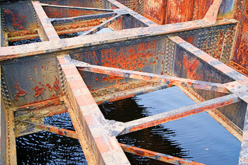 Rusted bridge girders over water