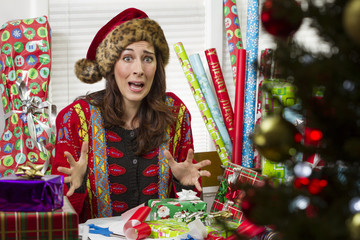 Woman wrapping Christmas presents, looking frustrated.