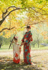 Woman and little girl in kimono walking in autumn Park