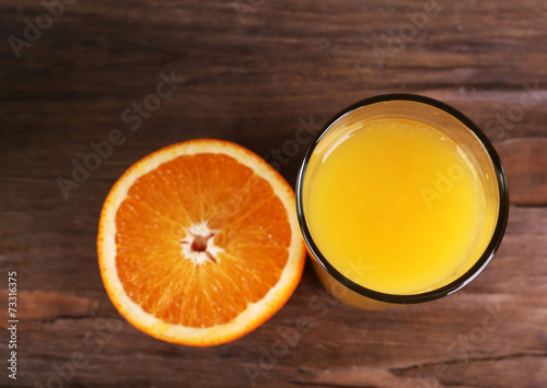 canvas print picture Glass of orange juice and fresh orange on wooden background
