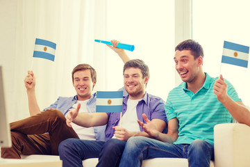 happy male friends with flags and vuvuzela