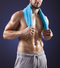 Fitness man holding a blue towel against dark background