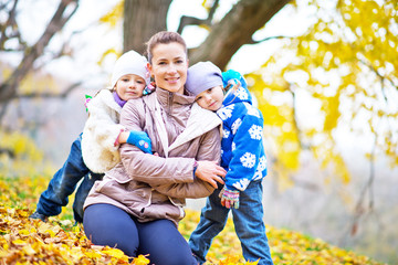 mother and her doughters in autumn park