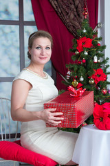 Woman with gift box under tree at home